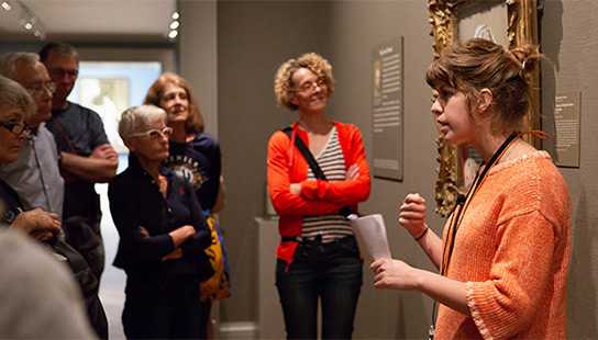 woman speaking to a group about a painting